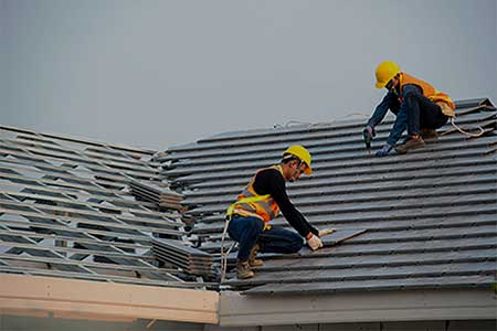 Roofers with safety harnesses